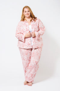 Plus Size Model wearing 100% cotton pyjamas with long sleeves and long pant length.  The fabric is white with a floral red print.