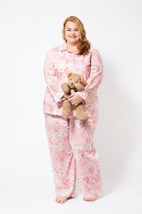 Plus Size Model wearing 100% cotton pyjamas with long sleeves and long pants.  The fabric is white with a floral red print.  She is holding a teddy bear.