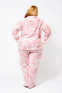 Back View of a Plus Size Model wearing 100% cotton pyjamas with long sleeves and long pants.  The fabric is white with a floral red print.