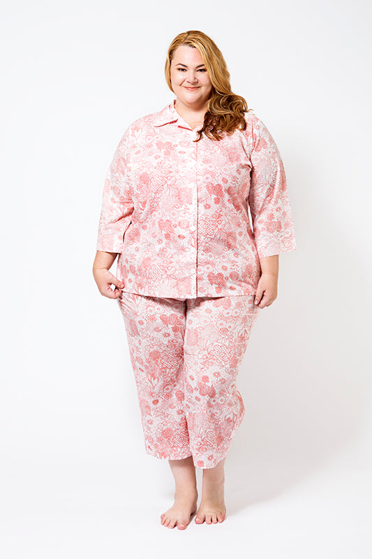 Plus Size Model wearing 100% cotton pyjamas with short sleeves and short pant length.  The fabric is white with a floral red print.