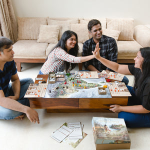 Two young women high five while playing a GoIndia Games board game together with their families
