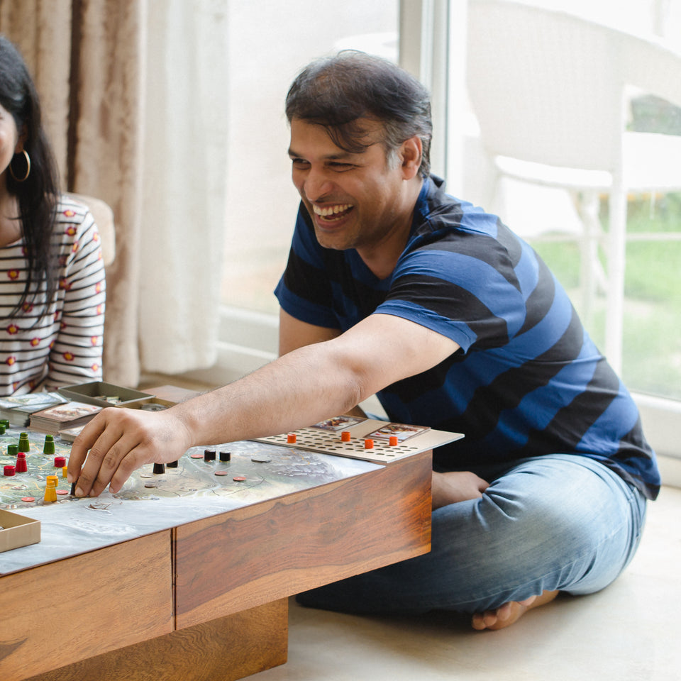 A young man laughs while placing a pawn on the game board of Bharata 600 BC