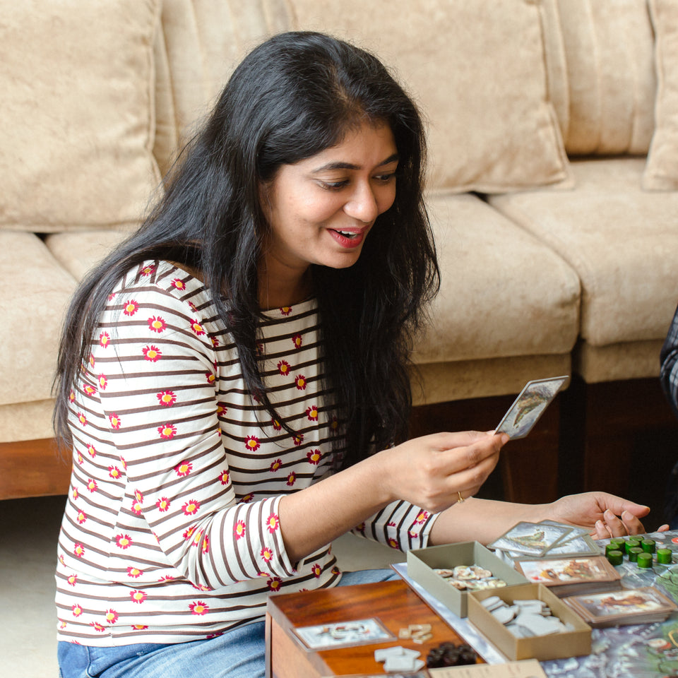 Young woman gazes at a playing card while playing a GoIndia Games board game