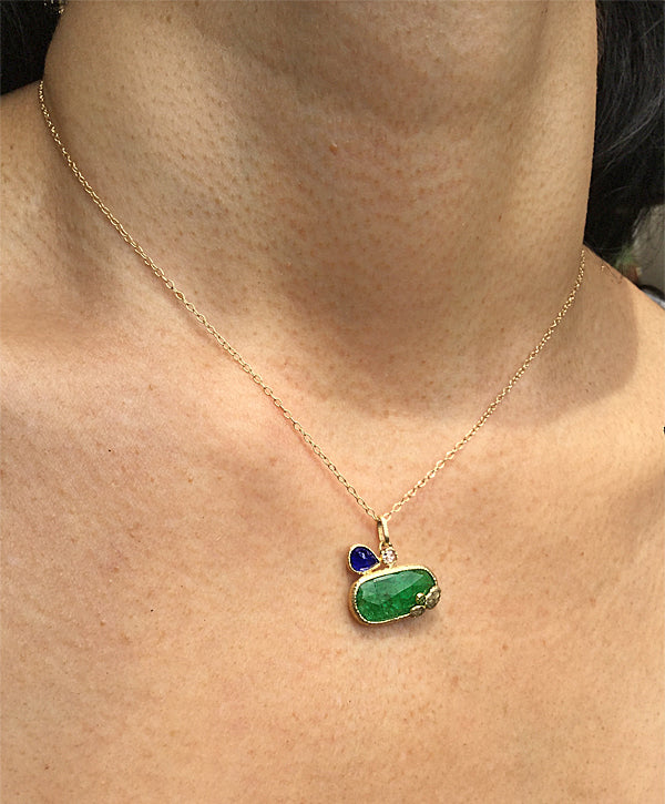 Free form emerald pendant with pear shaped sapphire on neck