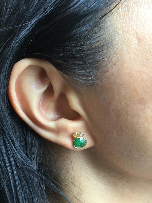 emerald stud earring on ear