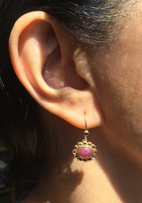 opaque ruby earrings in 18k gold with black diamonds on ear