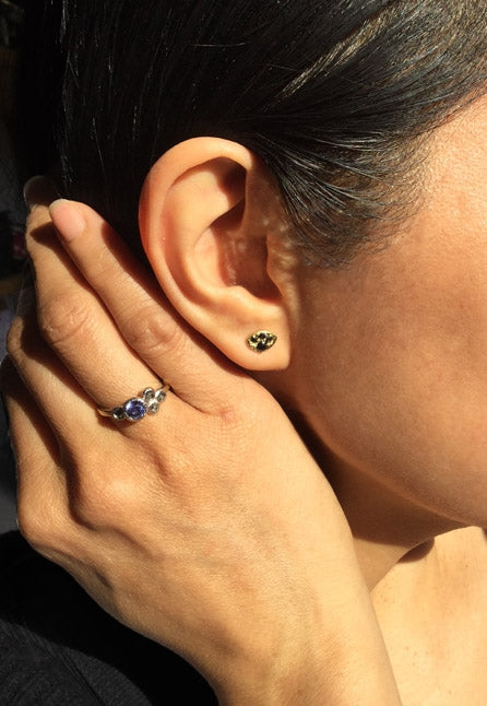 Black diamond stud earrings worn with purple sapphire ring