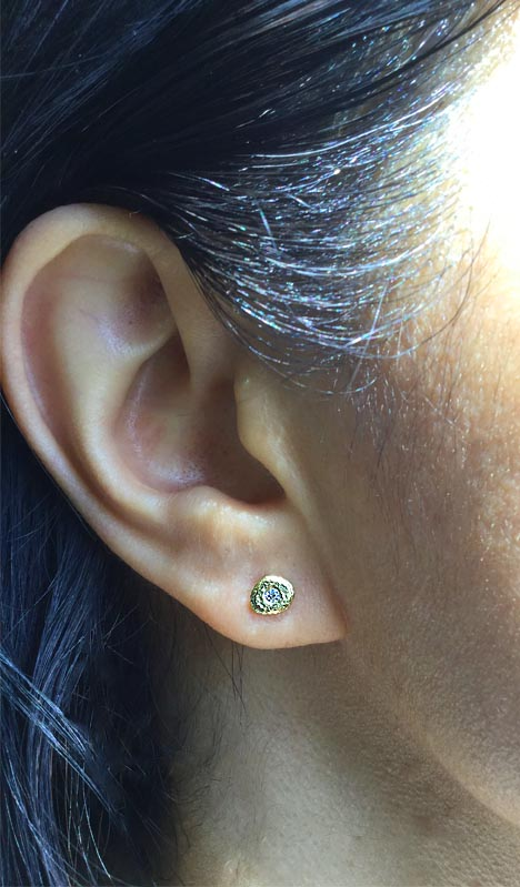 Single Pebble stud earrings in 18k gold with diamond on ear