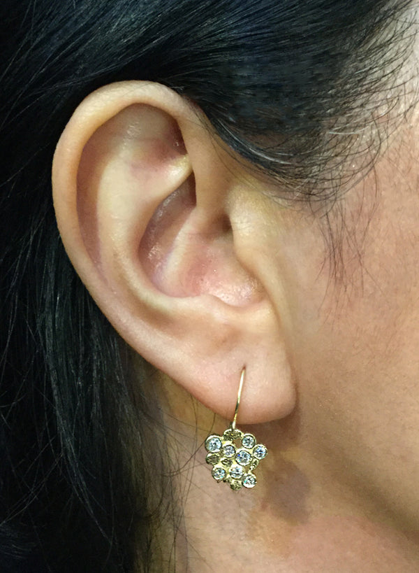Diamond cluster stud earrings on ear