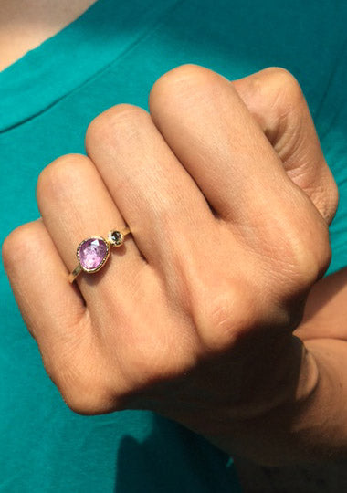 pink sapphire ring with a salt and pepper diamond on hand