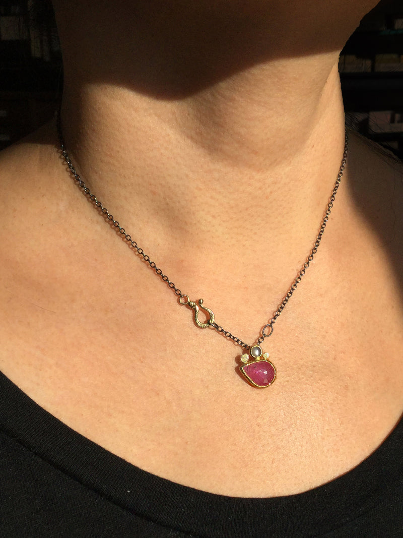 Pear shaped ruby pendant on neck