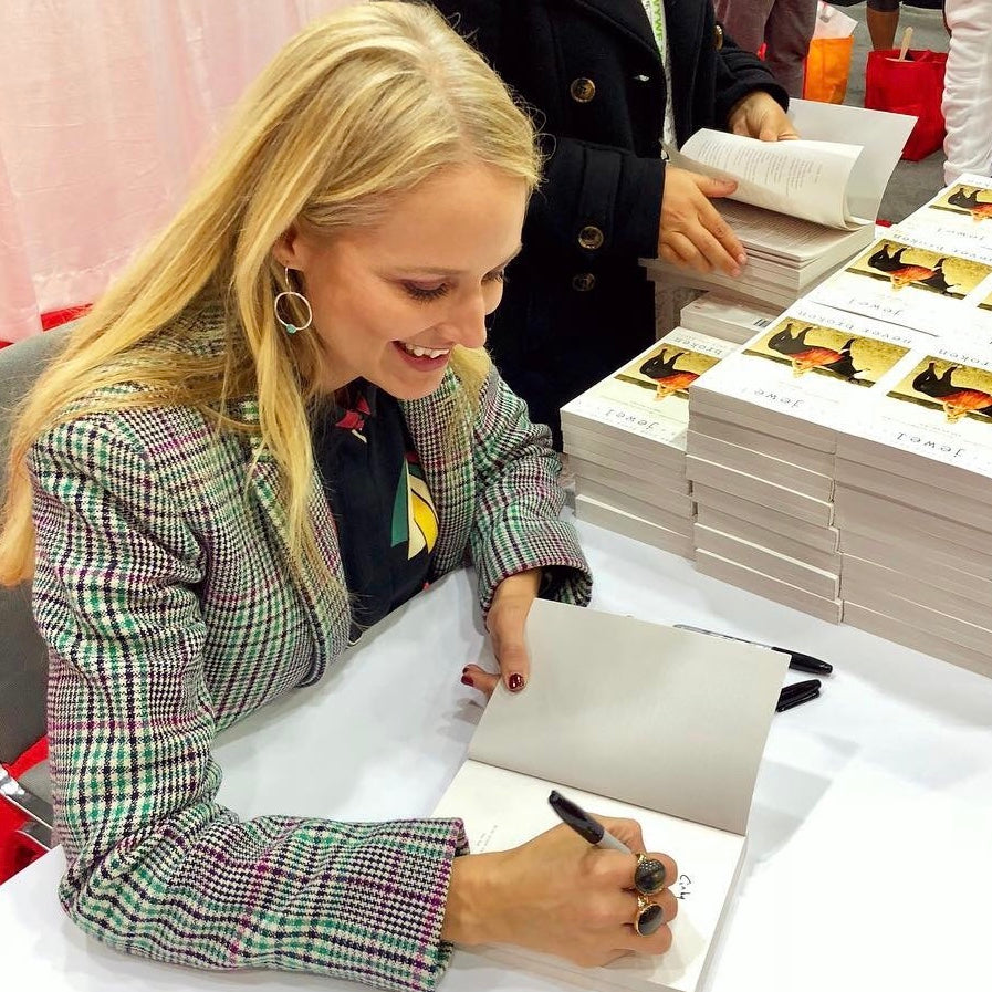 Jewel autographing her Never Broken books wearing Circle of Life earrings from Songlines by Jewel Handmade Collection