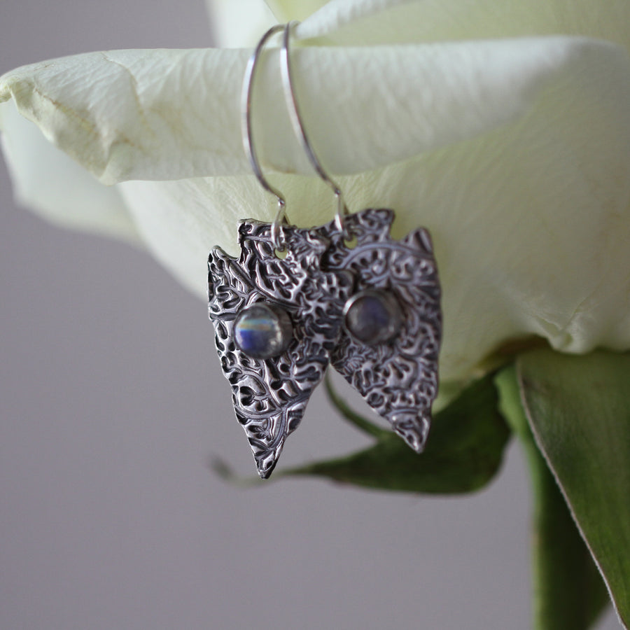 Handmade sterling silver arrowhead earrings hanging on the petal of a white rose