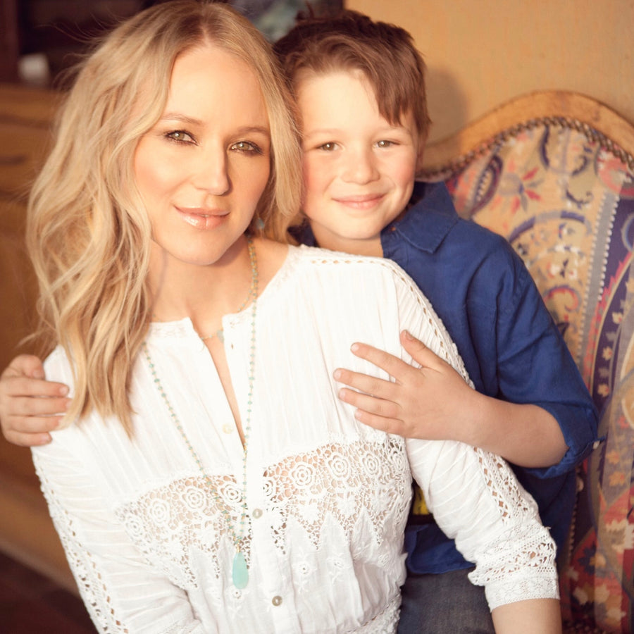 Singer Jewel with her son Kase as she models a long blue faceted chalcedony tear drop pendant on blue quartz and apatite bead chain