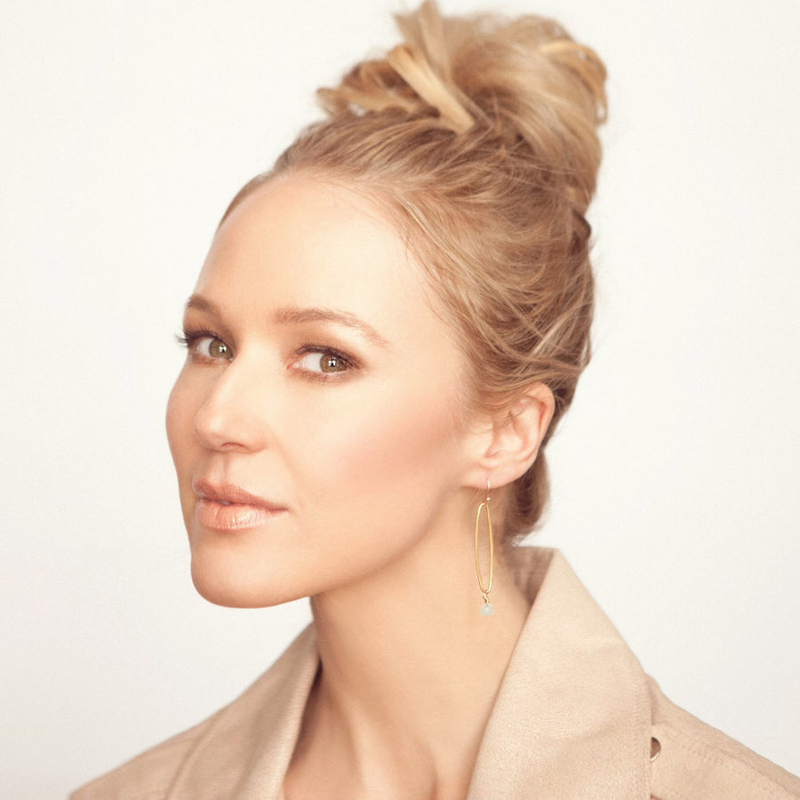 Jewel in an updo modeling long gold vermeil organic oval earrings with blue chalcedony drops