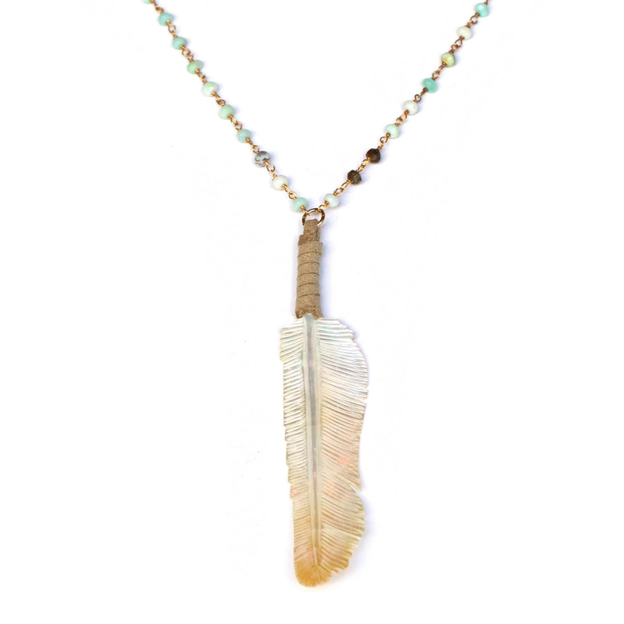 Handcarved yellow lip shell feather pendant with blue opal bead chain on white backdrop