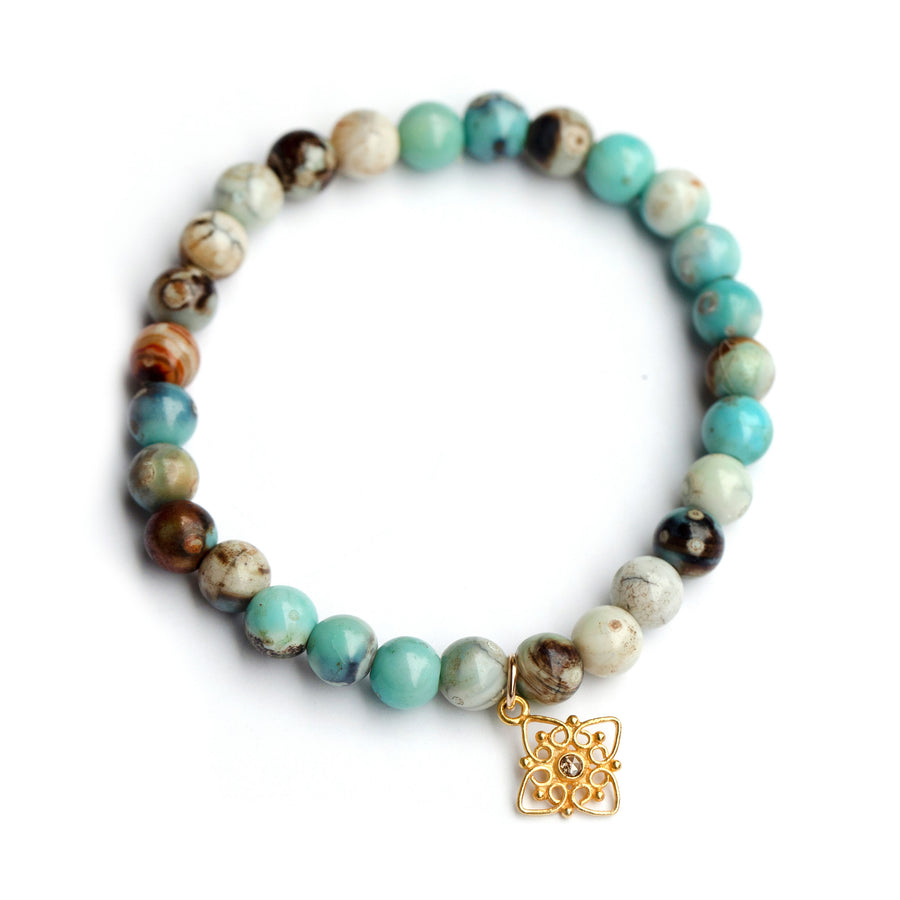 Blue jasper bead stretch bracelet with gold filigree star charm accented with a set polki diamond.