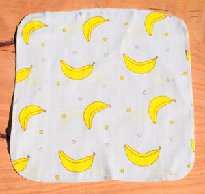 baby handkerchief with banana print laid out on table