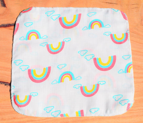 baby handkerchief with rainbow print laid out on table