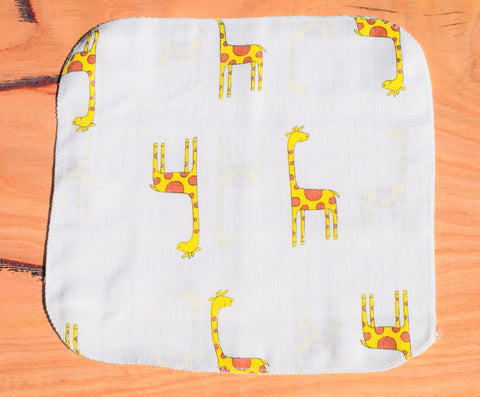 baby handkerchief with giraffe print laid out on table