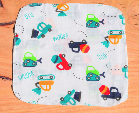 baby handkerchief with trucks and tractors print laid out on table
