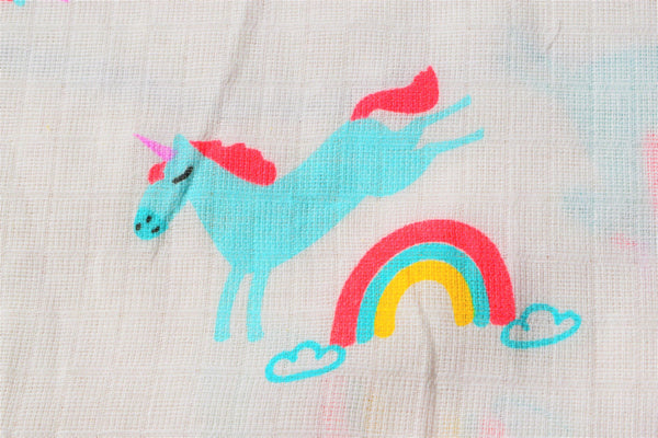 cotton fabric printed with a unicorn jumping over a rainbow