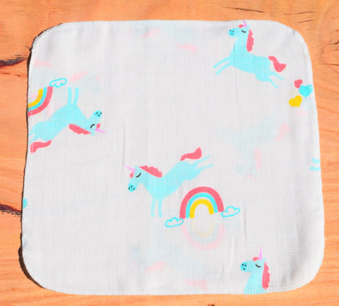 baby handkerchief with unicorn and rainbow print laid out on table