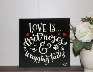 6x6x1 wood panel sign. Painted black background with white text - Love is wet noses & wagging tails, with red hearts.