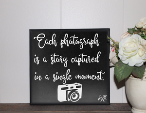 6x6x1 wood panel sign. Painted black background with white script text - each photograph is a story captured in a single moment with a retro camera.