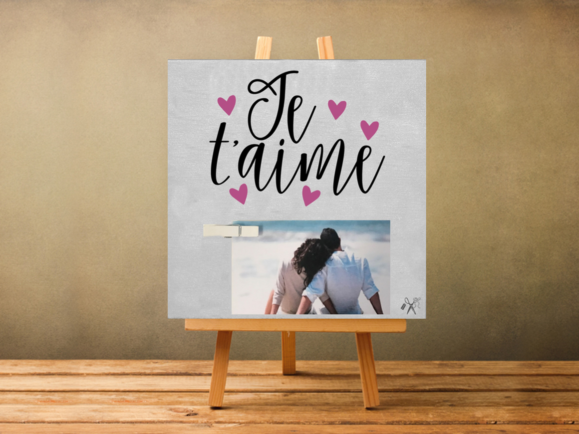 6x6x1 wood panel sign. Pained white background with black script text - Je taimi with pink hearts. Also includes a small, white close pin to attach a photo.