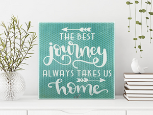 6x6x1 wood panel sign. Blueish green background with white text - The best journey always takes us home with arrows.