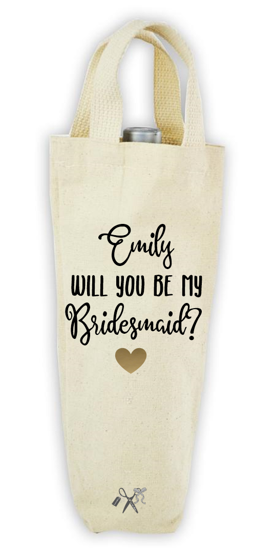Cotton/poly canvas wine bottle tote with webbed handles. Heat transfer black vinyl professionally applied. Text is personalized with name - Will you be my bridesmaid. Includes a gold heart.