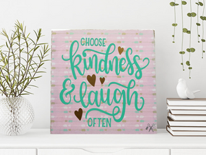 6x6x1 wood panel sign. Soft pink & gold background. Teal text - Choose Kindness & laugh often, with gold hearts.