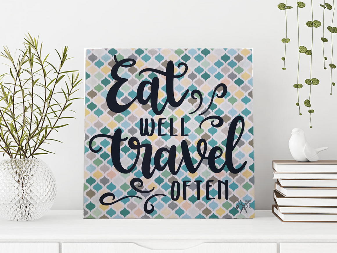 6x6x1 wood panel sign. Mosaic background in shades of blue. Text - Eat well and travel often.