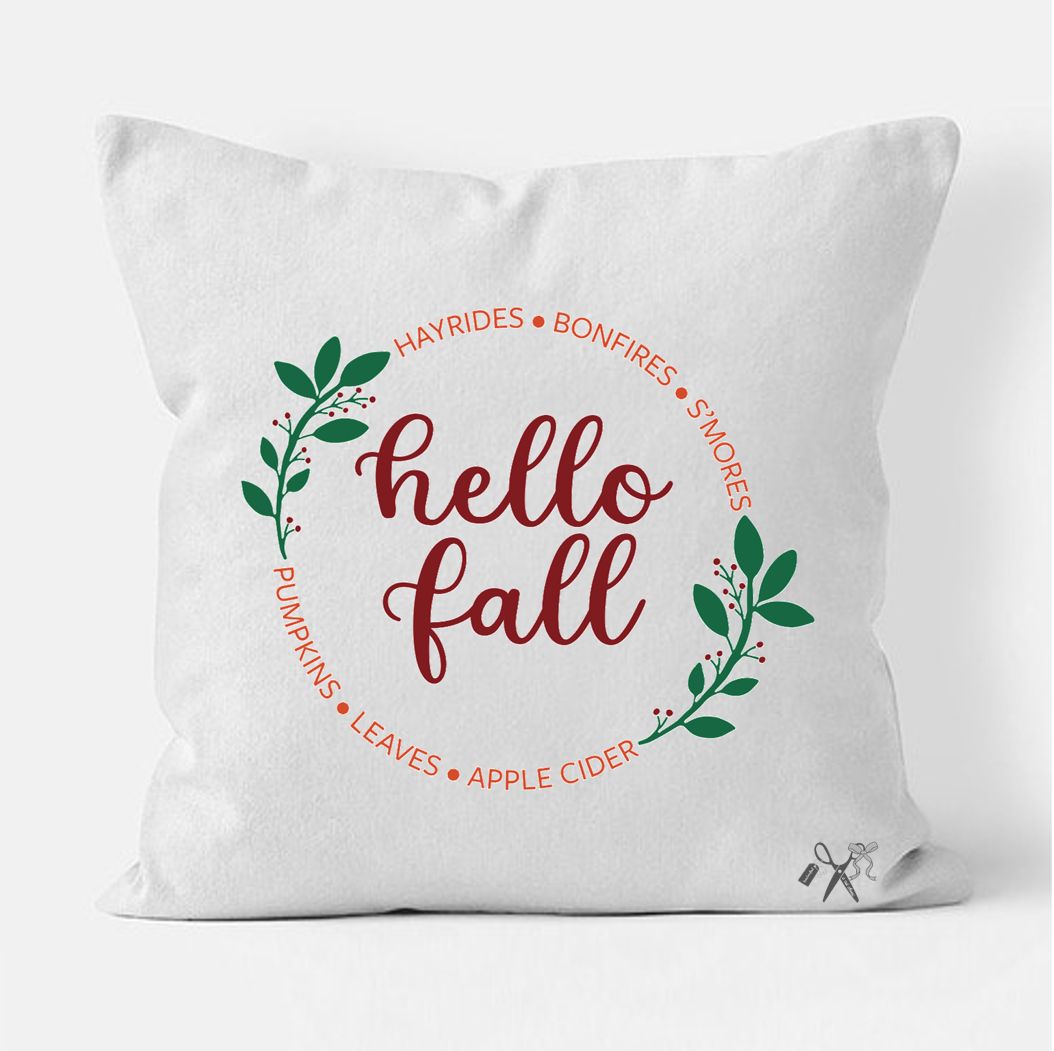 16x16 square, cotton, white pillow cover. Heat transfer vinyl professionally applied. Text - hello fall inside a circle of green laurels and fall related terms in orange.