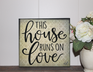 6x6x1 wood panel sign. Fleur de lis background with black text - This house runs on love.