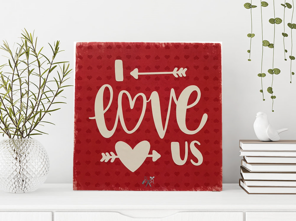 6x6x1 wood panel sign. Bright red background with white lettering - I love us with an arrow and heart.