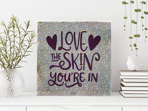 6x6x1 wood panel sign. Pale purple background with dark purple text - Love the skin you're in with big hearts.
