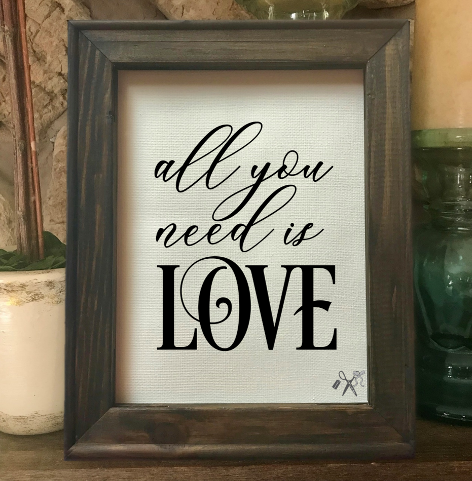 8x10 reverse canvas. Frame is dark walnut stained. Heat transfer vinyl in black, professionally applied with script text - all you need is love.