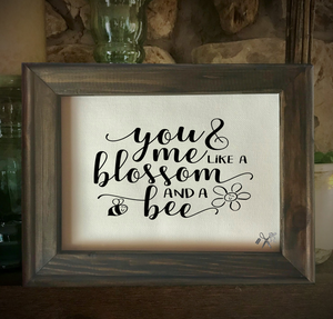 8x10 reverse canvas. Frame is dark walnut stained. Heat transfer vinyl in black, professionally applied with script text - you and me like a blossom and a bee.