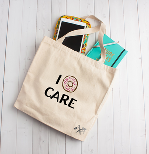 "14""W x 15""H x 4""D heavy canvas tote with 22"" webbed handles. Heat transfer vinyl professionally applied. Text is I (with a sprinkled image) donut care."