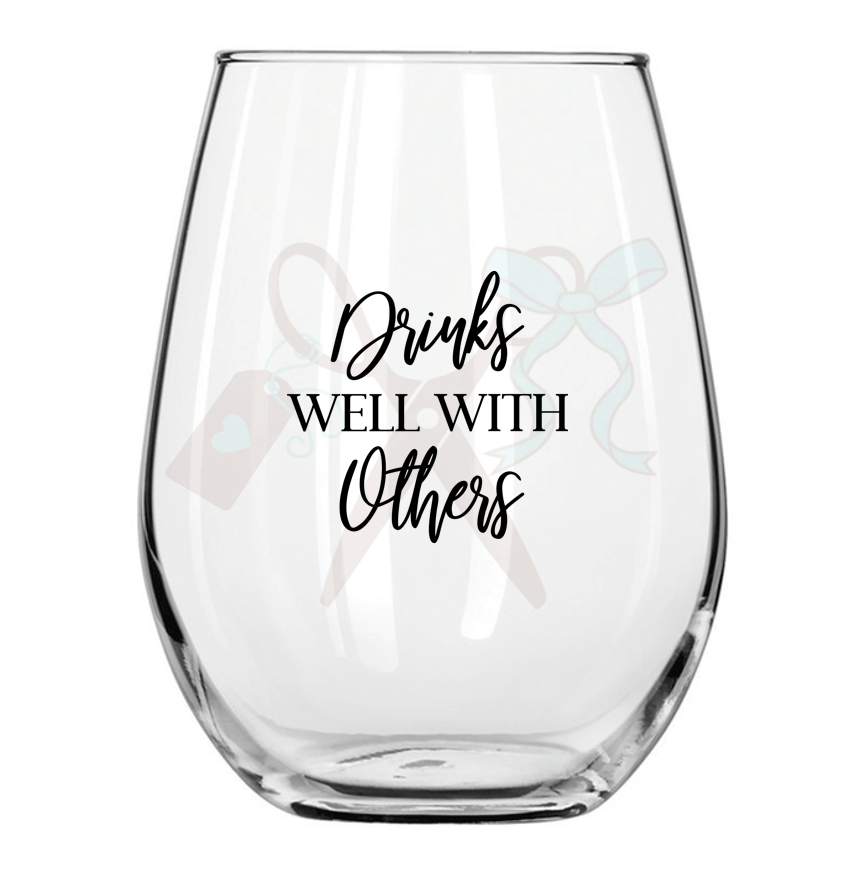 21oz stemless wineglass with black premium, permanent, vinyl application. Text - drinks well with others.