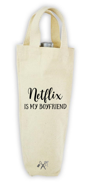 Cotton/poly canvas wine bottle tote with webbed handles. Heat transfer black vinyl professionally applied. Text - Netflix is my boyfriend.