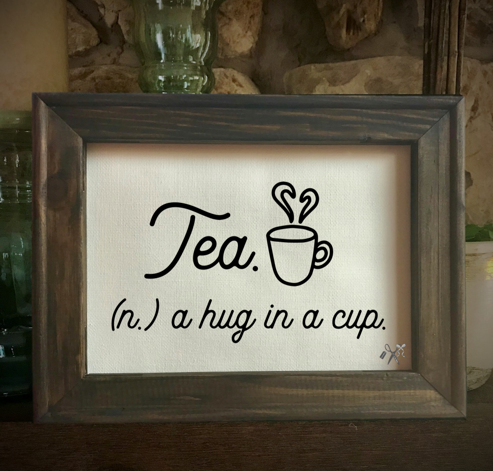 8x10 reverse canvas. Frame is dark walnut stained. Heat transfer vinyl in black, professionally applied as definition for tea as a hug in a cup. with a cup and steam forming a heart.