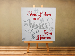 6x6x1 wood panel sign. Painted white background with red and silver glitter text - snowflakes are kisses from heaven with silver glitter snowflakes.