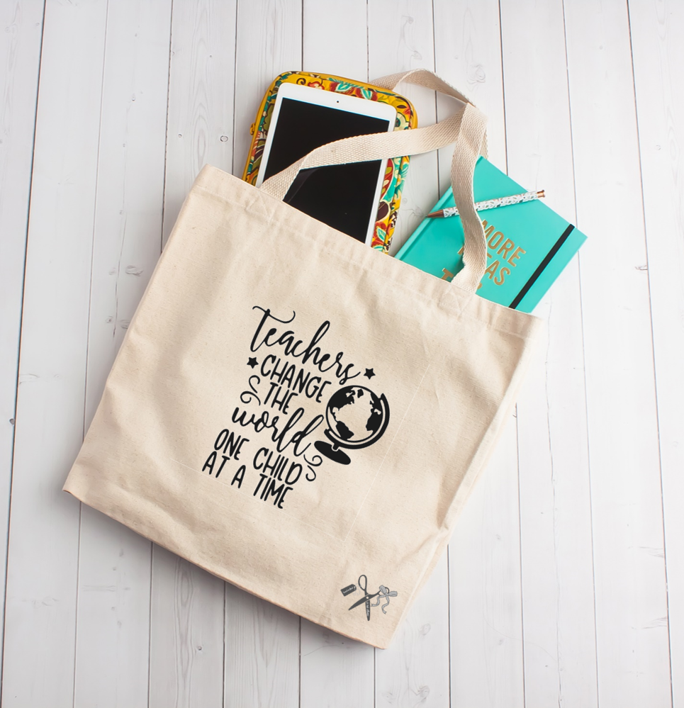 "14""W x 15""H x 4""D heavy canvas tote with 22"" webbed handles. Black heat transfer vinyl professionally applied. Includes text teachers change the world one child at a time with a globe image."