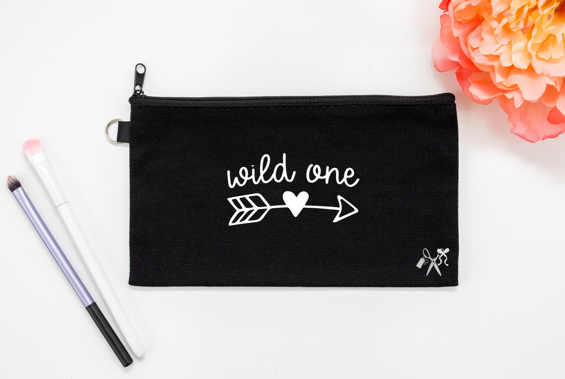 5x8 black cotton makeup bag. White text - wild one in script with arrow and heart.