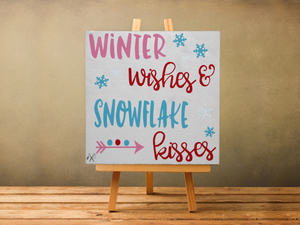 6x6x1 wood panel sign. Painted white background. Pink, read, and light blue text Winter wishes & snowflake kisses with snowflakes and arrow accents.