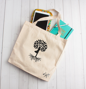 "14""W x 15""H x 4""D heavy canvas tote with 22"" webbed handles. Black heat transfer vinyl professionally applied. Image is a person standing in a yoga pose with roots being her feet and circle of leaves in the form of a tree around her head."