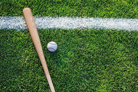 A wood baseball bat, and baseball lying on the grass, with a white stripe going by them.